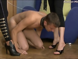 Slave guy on a leash licks feet of mistresses