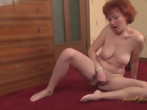 Shaved mature redhead rubs her cunt