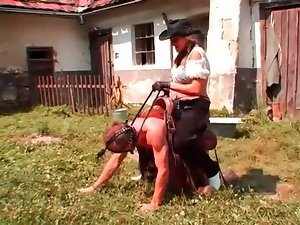 Cowgirl rides him like a pony outdoors