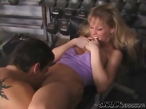 Fit blonde with fake tits sucks cock in gym