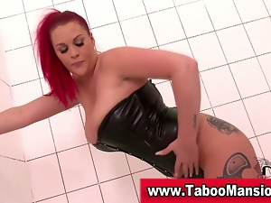 Redhead domme in leather teases and poses
