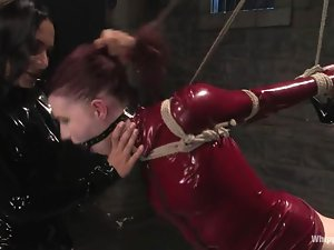 Slave in red latex is being painsulted by a brunette mistress