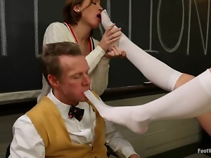 Two babes in school uniform give a footjob to their teacher