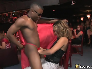A black stud gets his shaft sucked by a few women in a club