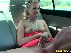Blonde milf shows tits and cunt in the car