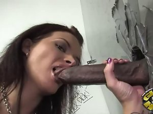 Busty brunette sucking cock through a hole