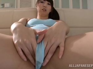 Japanese girl in a swimsuit fondles her pussy lying on a sofa