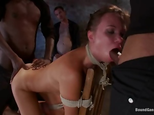 Sexy brunette gets tied up and fucked by a few men in a basement