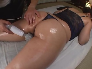 Oiled up Japanese chick gets her pussy toyed with a vibrator