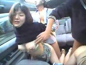 Two slutty Japanese milfs share a hard dick in a car