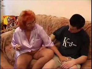 Lewd redhead granny plays with some young guy's hard cock