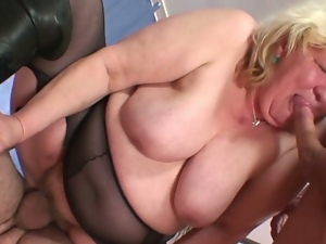 Huge titted horny grandma gets treat by two cocks