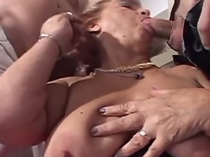 Naughty mature gets banged by two studs