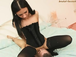 Skinny beauty in corset sits on his face
