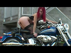 Red-haired biker in thrilling striptease