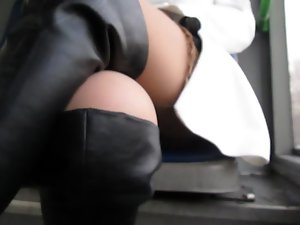 Lassie in ebony leather boots flashing stockings in a bus