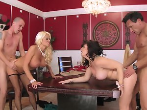 A tempting blonde and a dark haired are swapping partners on the wooden table