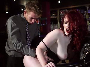 A redhead with large hooters is handling a dick in a bar