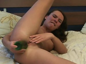 A large green bottle is getting placed inside a fresh vagina