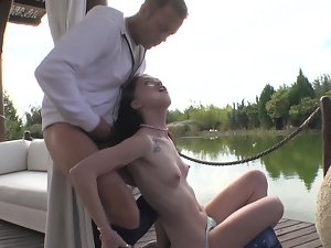 A dark haired is by the lake and she is receiving a shaft inside