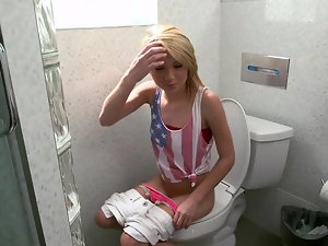 Tempting blonde is caught licking a phallus in the bathroom on the toilet