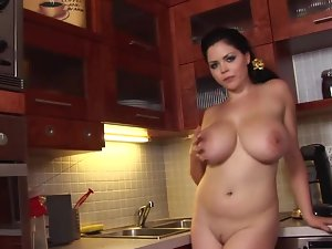 A heavy cutie is in the kitchen and she is playing with her large knockers