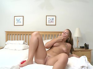 A sexual cunt undresses herself and plays with her pussy on the bed