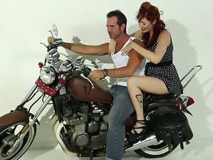 A redhead that has large knockers is getting screwed on the bike