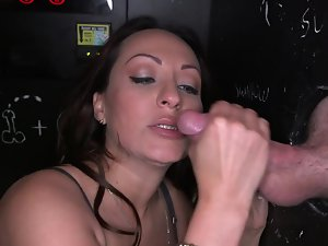 Chesty dark haired is licking dick in a glory hole and gets a load