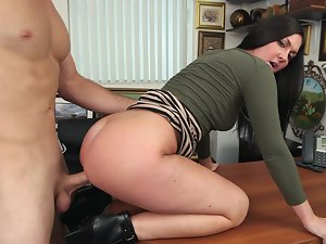 Sexual whore is shaking her butt on the office table in front of us
